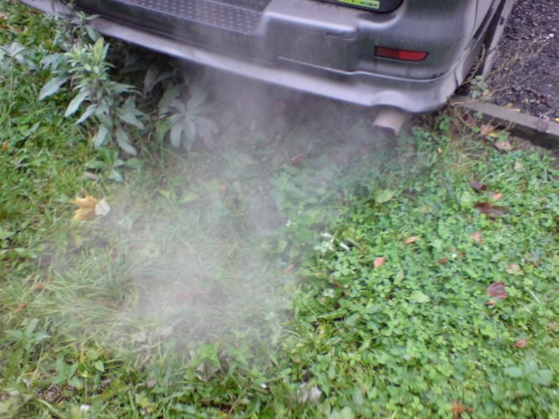 Сизый дым идет из глушителя
