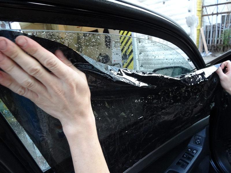 На снимке процесс тонирования бокового стекла