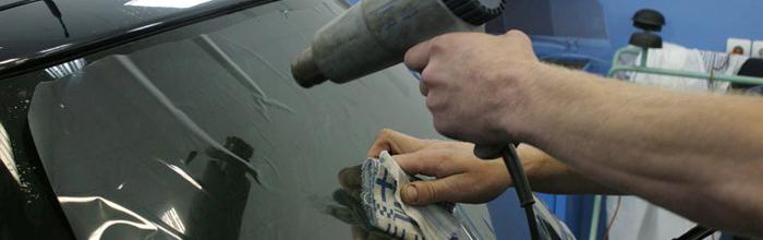 На фотографии процесс нанесения тонировки на стекло